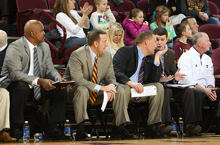 Men's basketball assistant coaches Kevin Gamble, Kyle Gerdeman, and Jeff Smith sit together in the second half against Eastern Michigan on Saturday, Jan. 18, 2014, at McGuirk Arena. (Photo | Danielle Duval)
