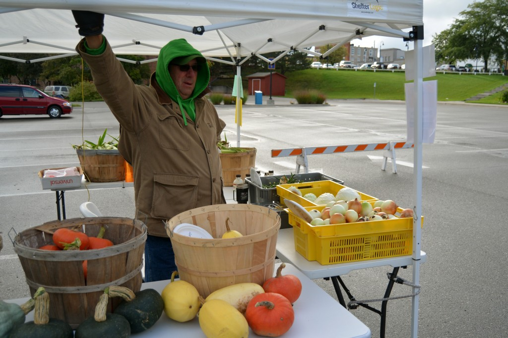 Dave Whitehead waits at his stand at the Farmers' Market, located behind City Hall, for customers to arrive on the slow and cold morning of Saturday, Sept. 13, 2014. (Photo | Andrea Henk)