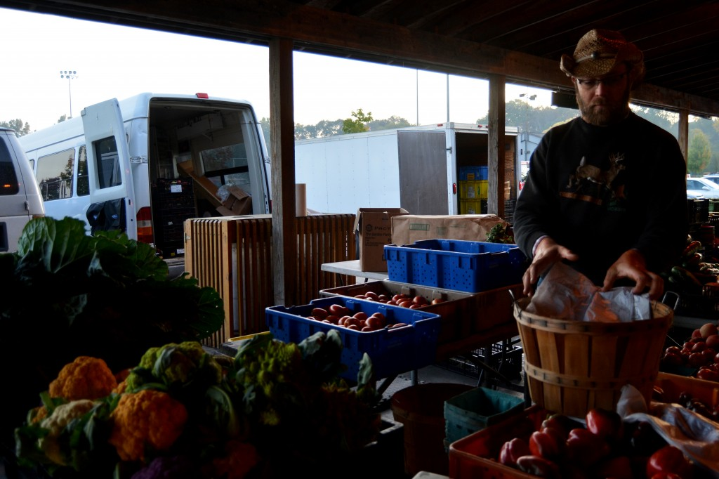 On the morning of Sept. 25, 2014, Isaac Martin prepares his stand at the Mount Pleasant Farmers' Market located at Island Park. Martin runs more than one farm and he sells different foods from each one. (Photo | Andrea Henk)