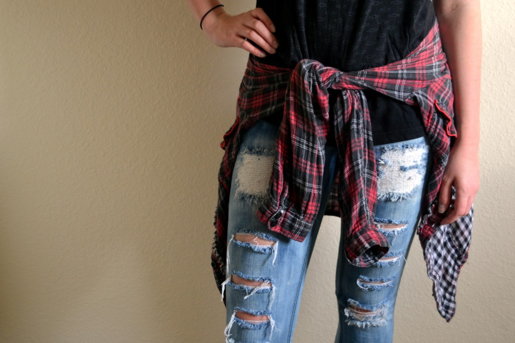 Brianna Clippert rocks a plaid flannel around her waist and ripped jeans, typical 90s grunge fashion. (Photo | Andrea Henk)