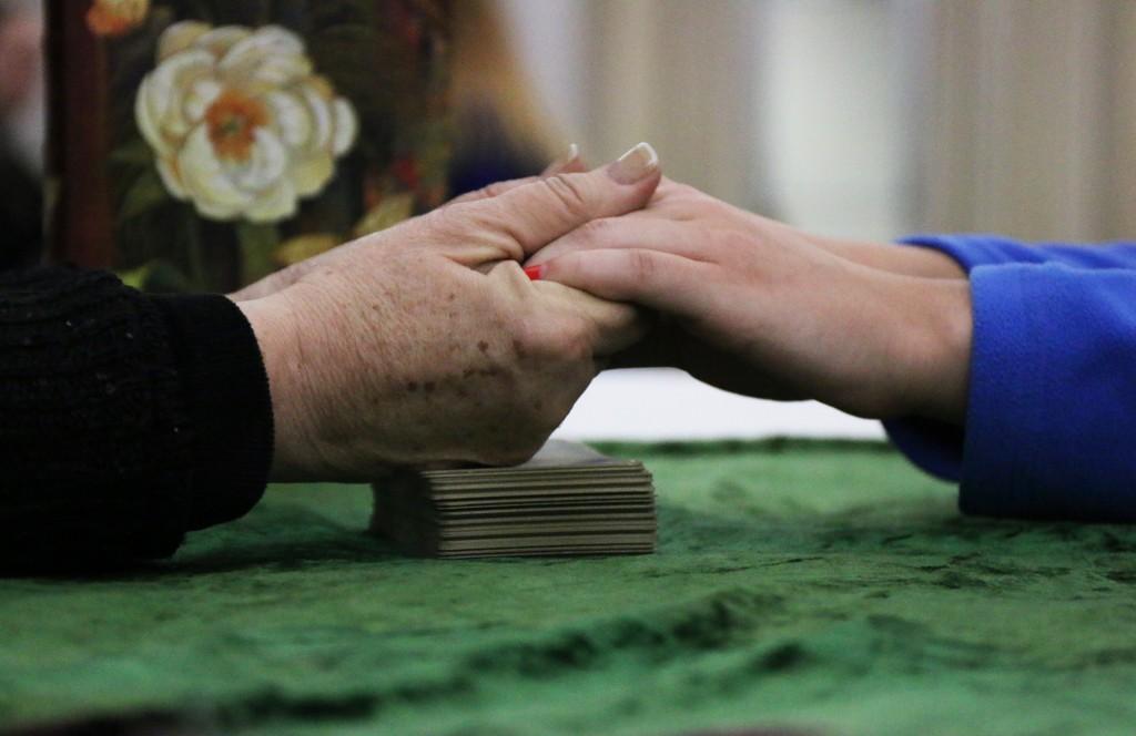 Psychic Pam Sekula holds Rowan Clark's hands as her reading starts at CMU Program Board's Psychic Fair on Thursday January 15, 2015. (Photo I Kaiti Chritz)