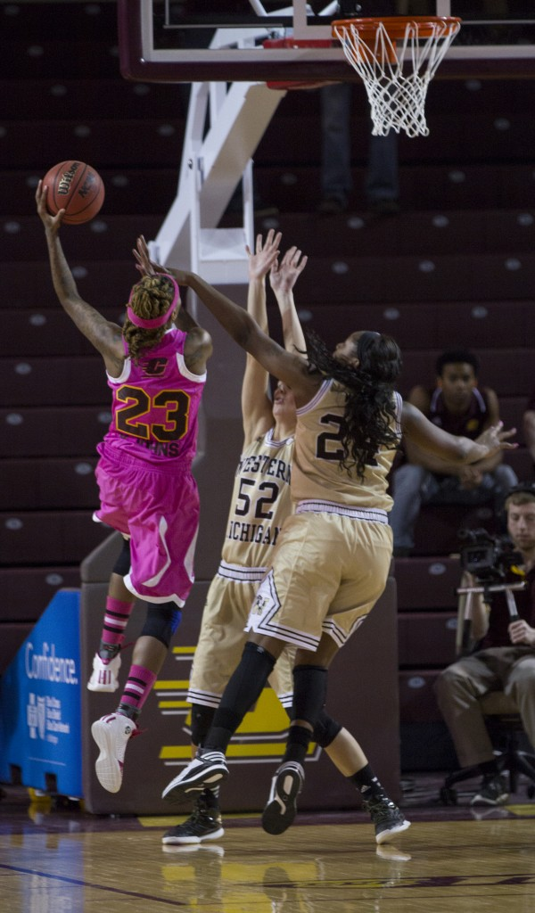 Central Michigan's Crystal Bradford, (23),drives to the hoop against Western Michigan'sMiracle Woods, (24), and Jessica Jessing, (52), during their game in McGuirk Arena, on the campus of Central Michigan University, Mt. Pleasant, Michigan, Saturday, February 21, 2015