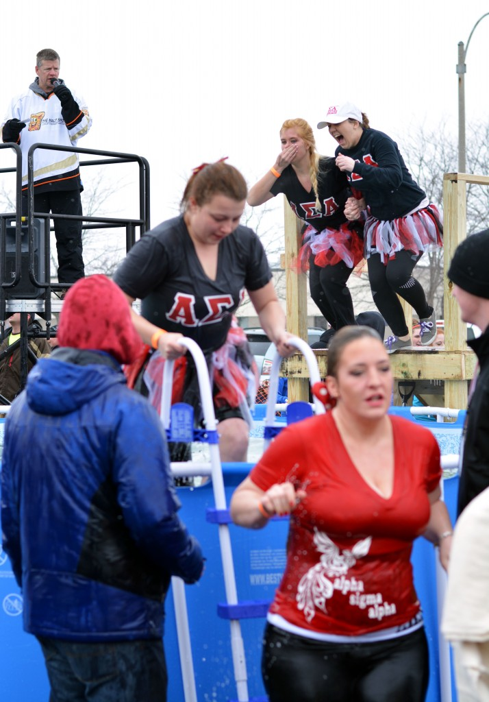 Two members of the Alpha Sigma Alpha sorority exit the pool while two other sorority members jump in after them during the Mount Pleasant Polar Plunge. (Photo | Andrea Henk)