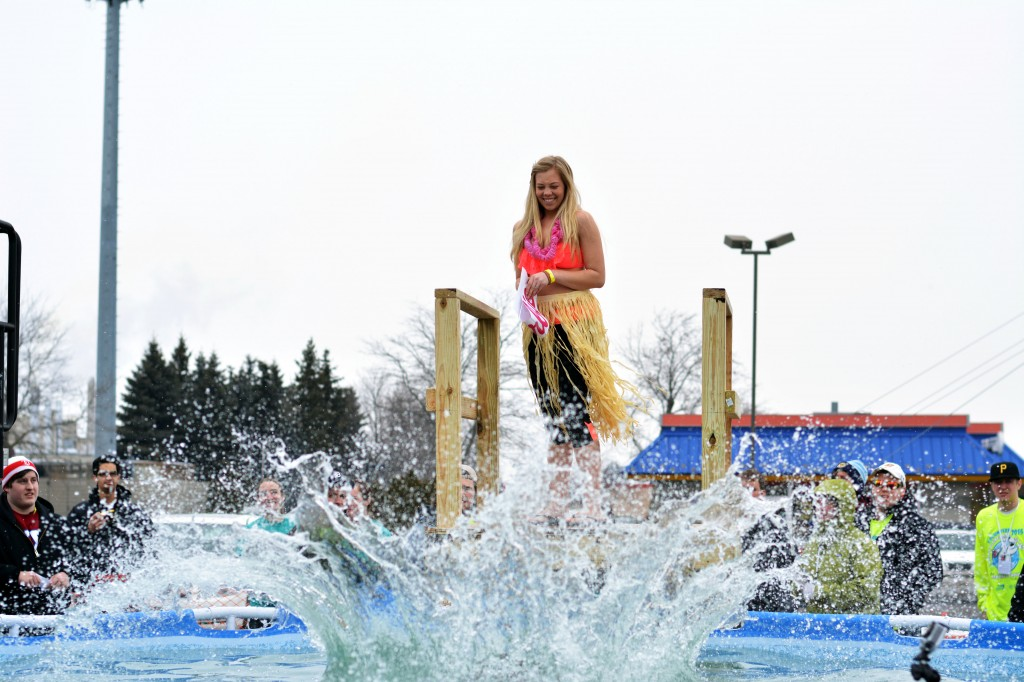 "A woman dressed as a ""Barbie"" smiles as her teammate, who was dressed as ""Ken,"" causes a great splash during the Mount Pleasant Polar Plunge. (Photo 
