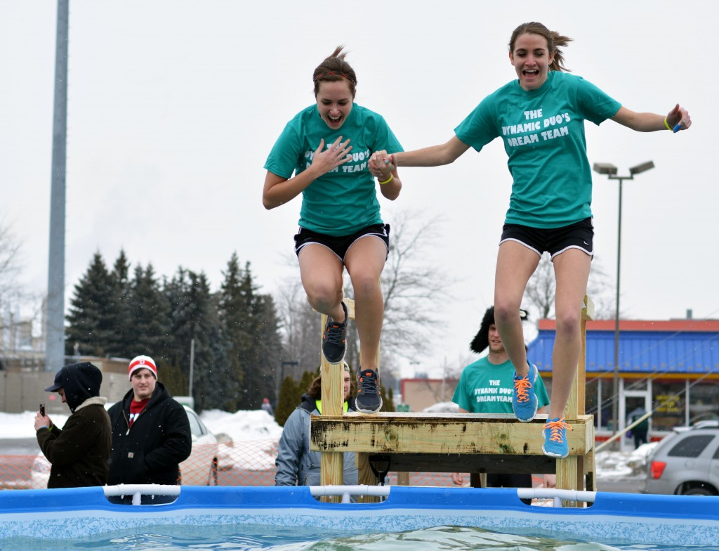 Two participants of the Mount Pleasant Polar Plunge hold hands as they jump. (Photo | Andrea Henk)