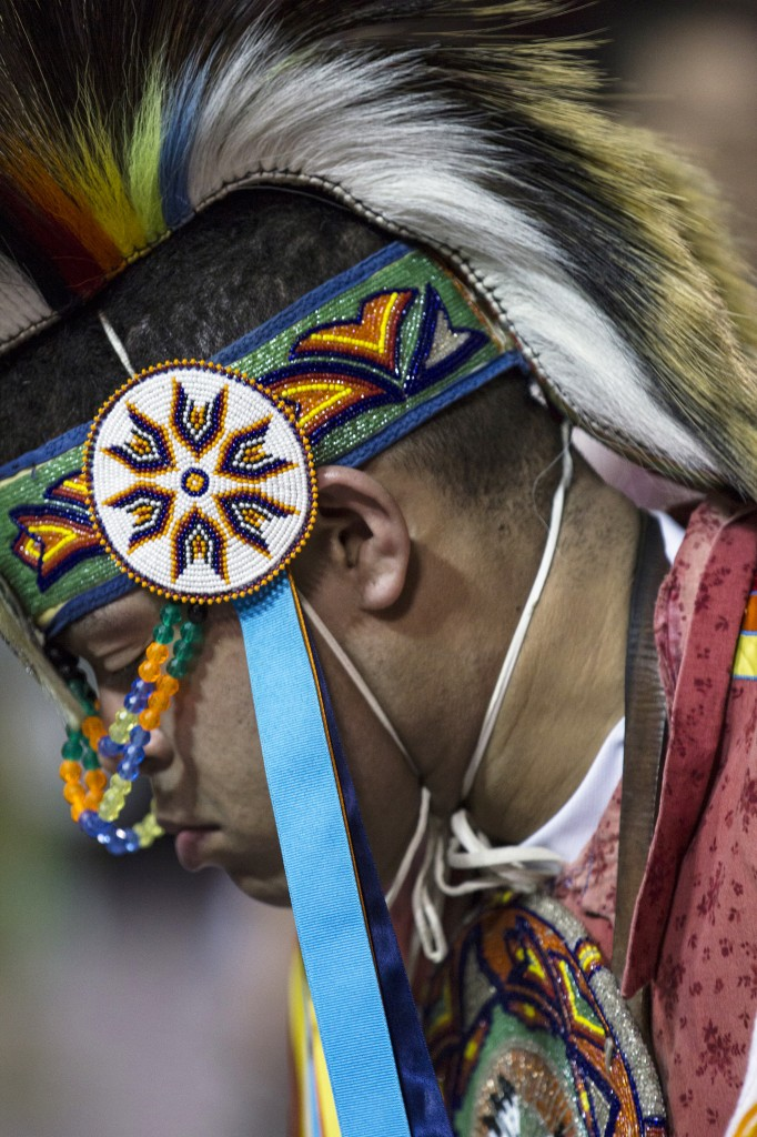 A Native American dancer looks down and pauses while dancing during the Anishinaabe Pow wow in McGuirk Arena. (Photo I Rich Drummond)