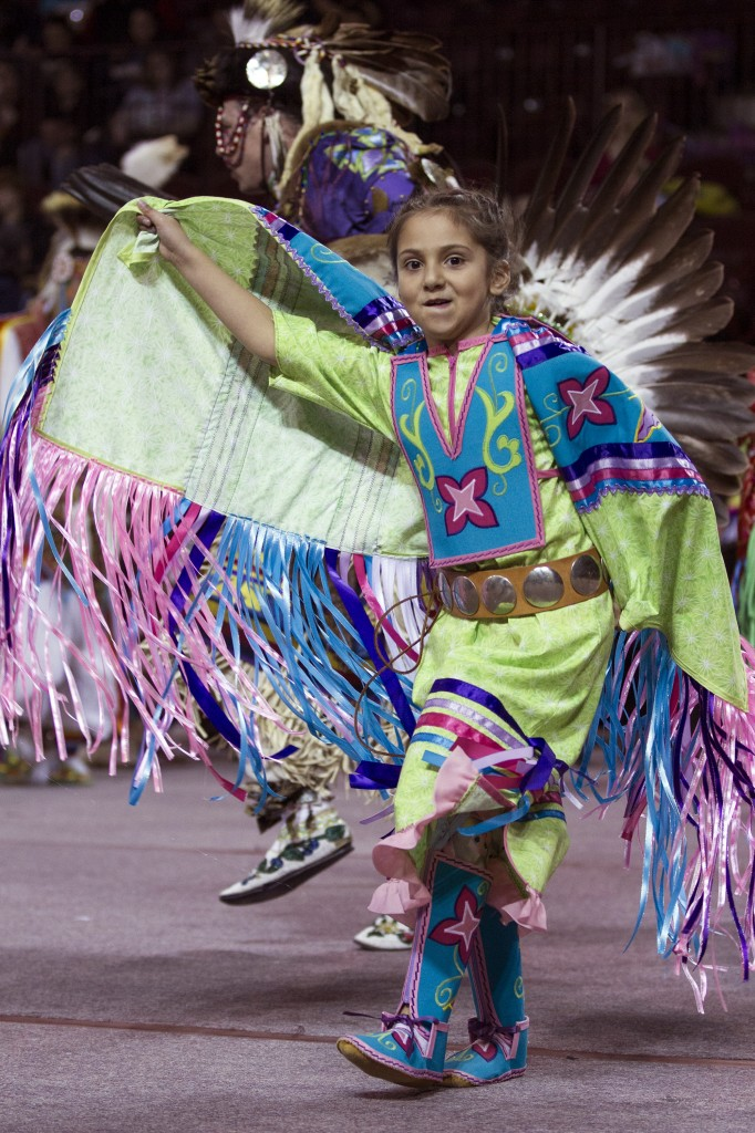 A young dancer raises her arm while dancing in her regalia during the Anishinaabe Pow wow in McGuirk Arena. (Photo I Rich Drummond)