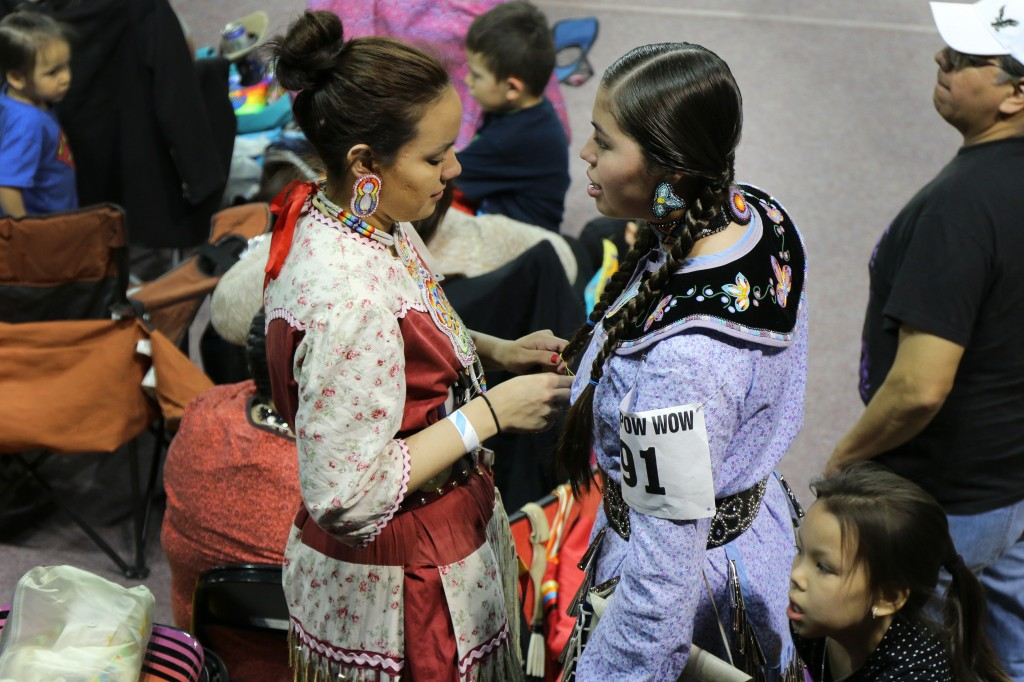 Ayascay Schuyler (left) braids the hair of her niece Maya Schuyler (right) before competing at the 26th Annual Celebrating Life Pow wow. (Photo I Kaiti Chritz)