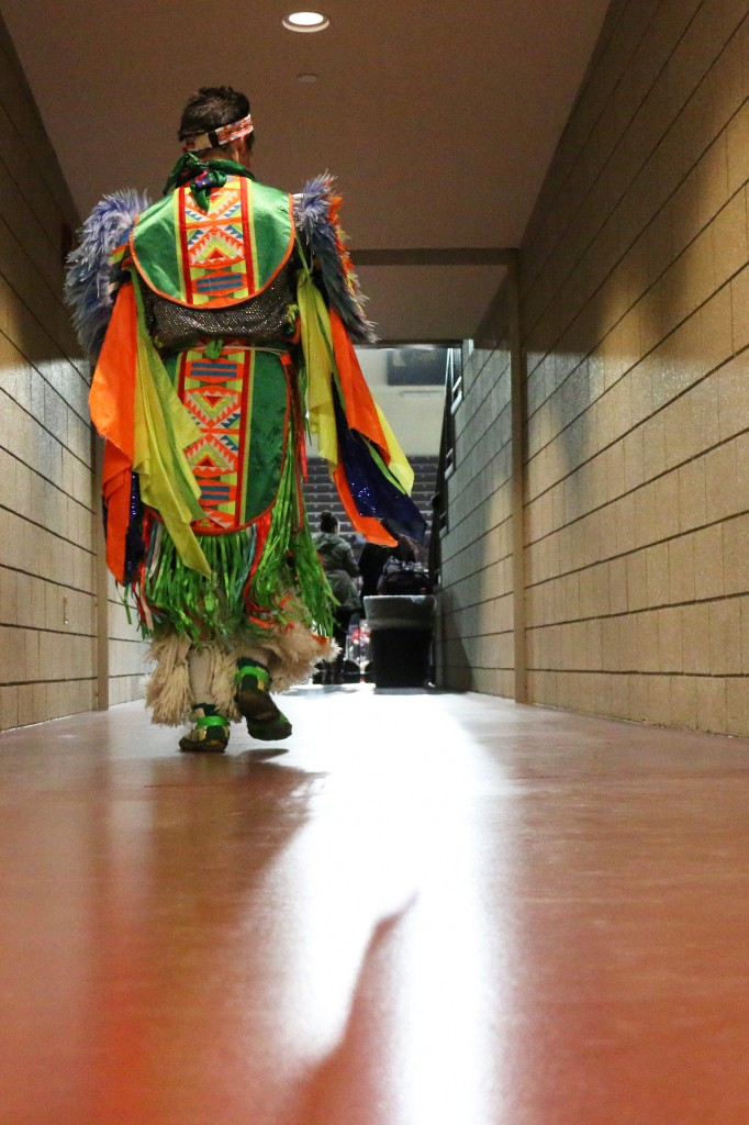 A dancer enters McGuirk Arena before the competition starts at the 26th Annual Celebrating Life Pow wow. (Photo I Kaiti Chritz)