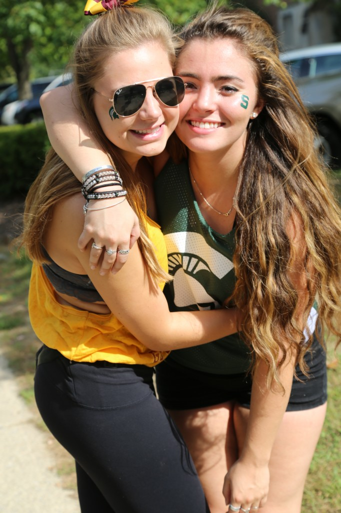 At the end of the day, students Rachel Stone (senior at CMU) and Simone Campbell (sophomore at MSU) set their rivalries aside to enjoy a fun day filled with friends, football, and free swag. The two pose for a picture on Saturday, September 26, 2015 in East Lansing.