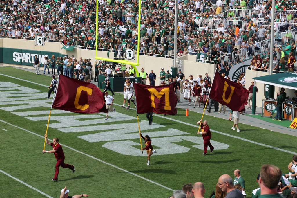 Central Michigan University students raise maroon and gold flags as they run across the field, welcoming the football players at Spartan Stadium Saturday, September 26, 2015 in East Lansing, Michigan.