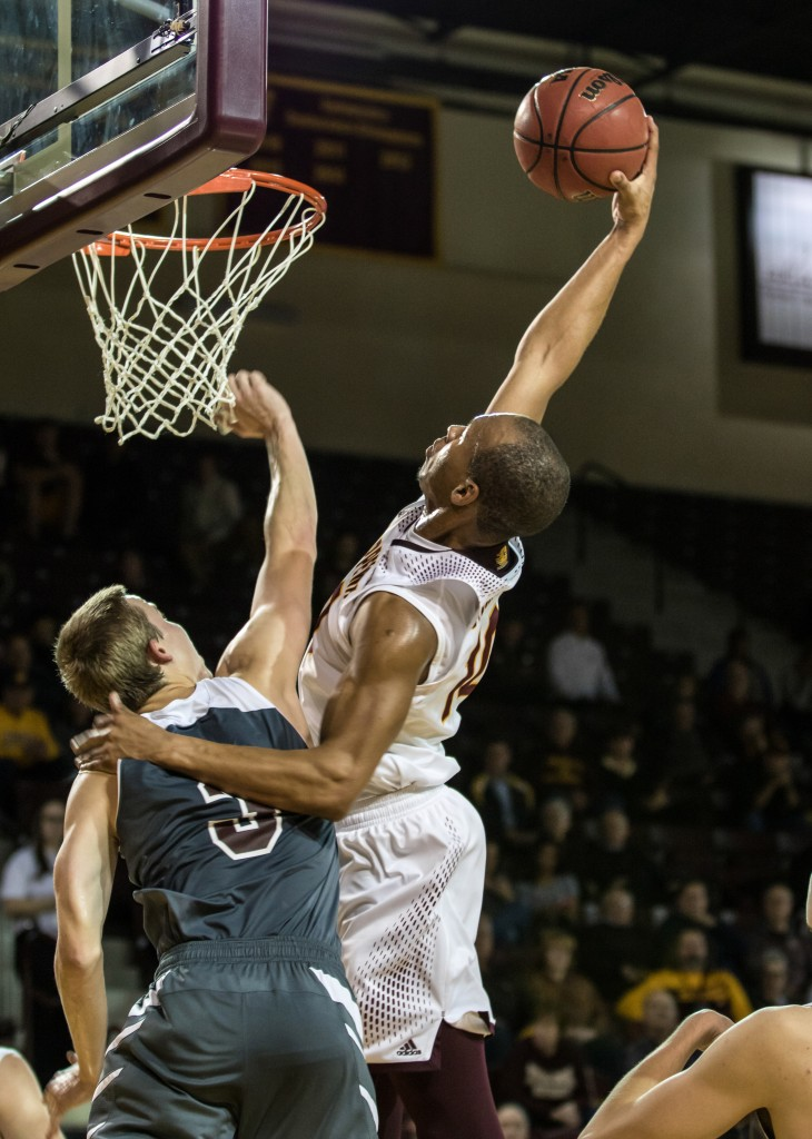 Austin Stewart, 10, posterizes Scott Nikodemski, 3, during the game against Alma College at McGuirk Arena in Mt. Pleasant, Michigan, Tuesday, November 17, 2015.