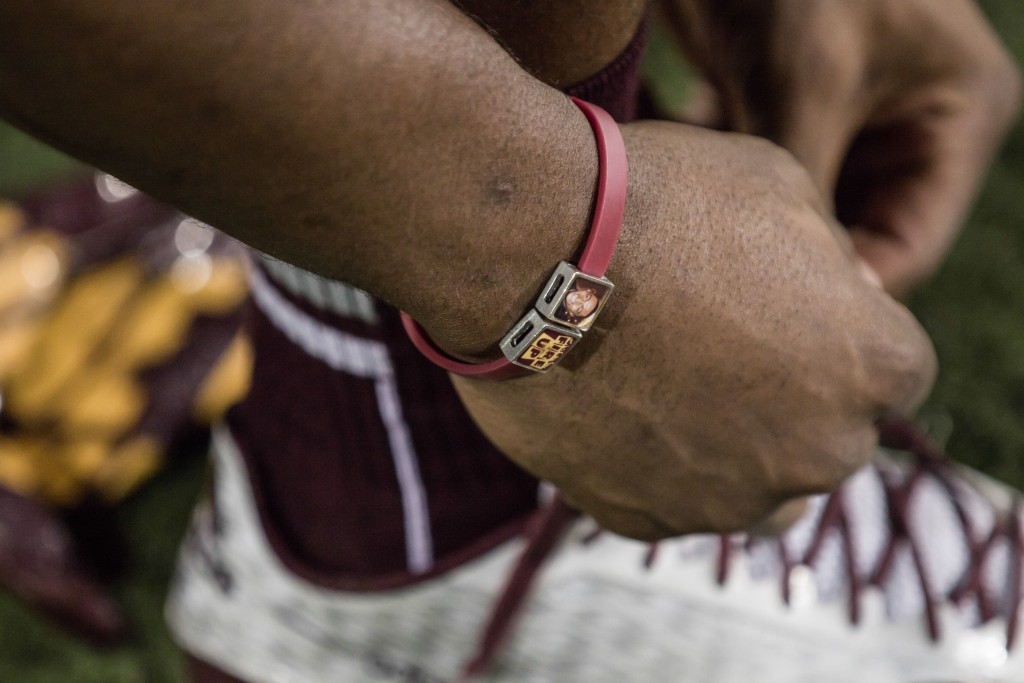 A player ties their shoes while wearing a braclet honroing the late Chippewa Derrick Nash before the game against the University of Toledo at Kelly Shorts Stadium, on the campus of Central Michigan University, Mt. Pleasant, Michigan, Tuesday, November 10, 2015.