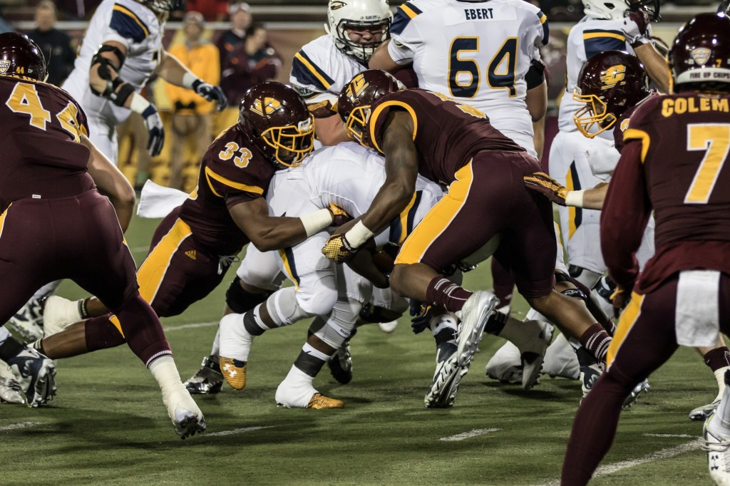 Tylree Waller, 33, and Kavon Frazier, 5, tackle Kareem Hunt, middle, during the game against the University of Toledo at Kelly Shorts Stadium, on the campus of Central Michigan University, Mt. Pleasant, Michigan, Tuesday, November 10, 2015.