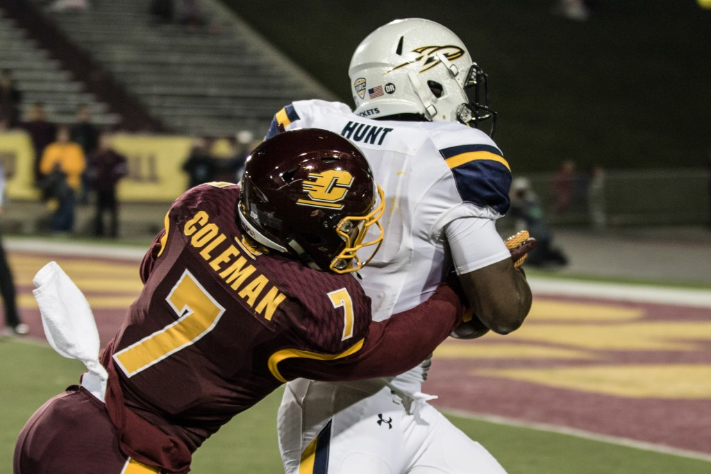 Amari Coleman, 7, tries to poke the ball from Kareem Hunt, 3, during the game against the University of Toledo at Kelly Shorts Stadium, on the campus of Central Michigan University, Mt. Pleasant, Michigan, Tuesday, November 10, 2015.