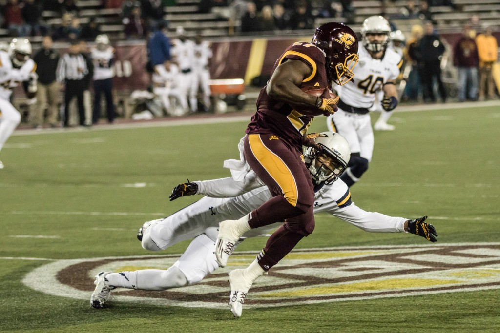 Trevon Mathis, 6, looks to wrap up Martez Walker, 27, during the game against the University of Toledo at Kelly Shorts Stadium, on the campus of Central Michigan University, Mt. Pleasant, Michigan, Tuesday, November 10, 2015.