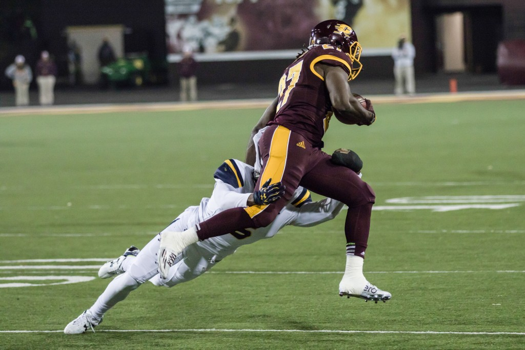 Trevon Mathis, 6, tackles Martez Walker, 27, during the game against the University of Toledo at Kelly Shorts Stadium, on the campus of Central Michigan University, Mt. Pleasant, Michigan, Tuesday, November 10, 2015.
