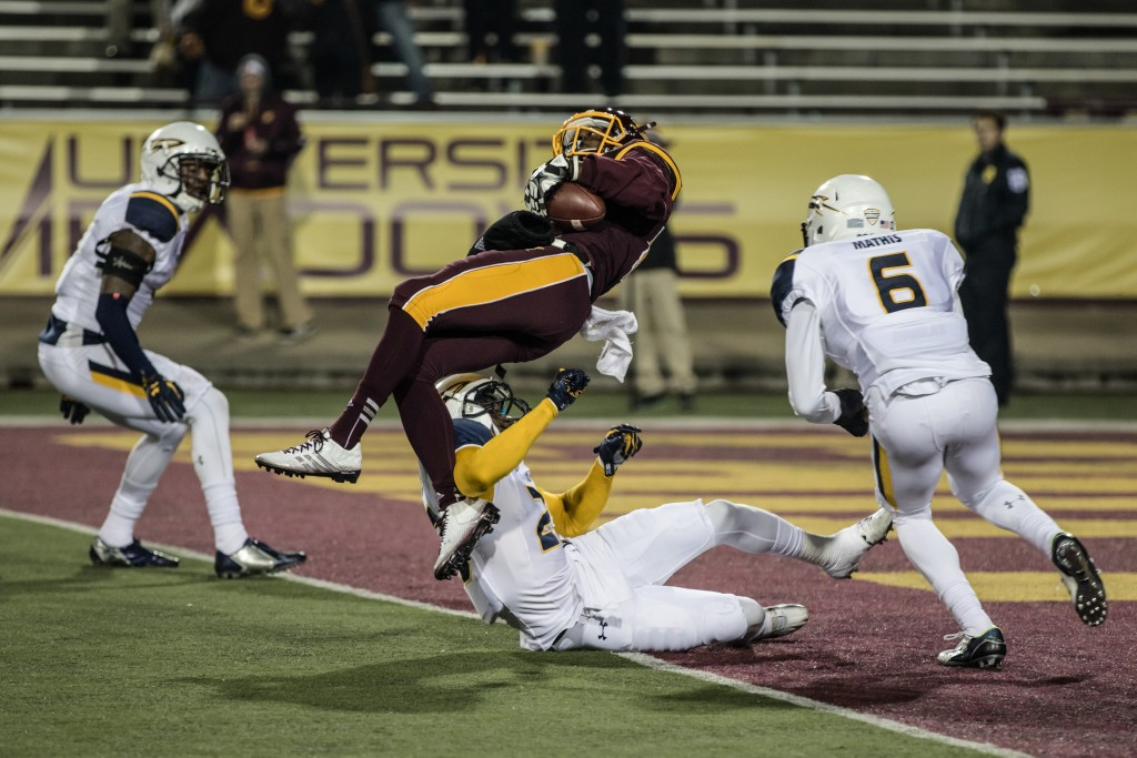 Corey Willis, middle, takes a big hit on his way into the endzone during the game against the University of Toledo at Kelly Shorts Stadium, on the campus of Central Michigan University, Mt. Pleasant, Michigan, Tuesday, November 10, 2015.