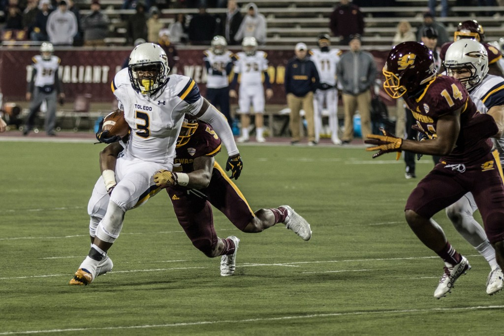 Kareem Hunt, 3, fights a tackle from Kavon Frazier, 5, during the game against the University of Toledo at Kelly Shorts Stadium, on the campus of Central Michigan University, Mt. Pleasant, Michigan, Tuesday, November 10, 2015.
