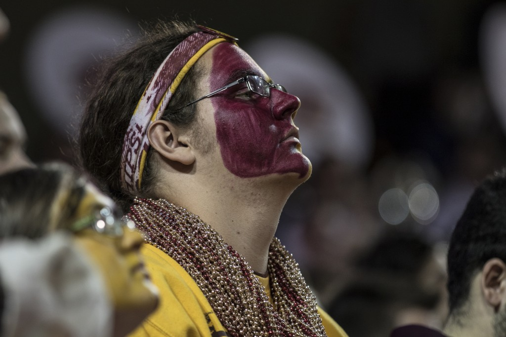 A CMU fan looks to the flag as the National Anthem is played before the game against Jacksonville State University in McGuirk Arena, on the campus of Central Michigan University, Mt. Pleasant, Michigan, Friday, November 13, 2015.