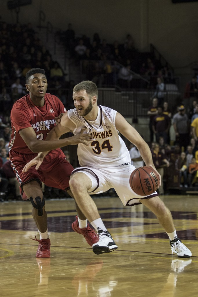 John Simons, 34, drives the lane against Christian Cunningham, 31, during the game against Jacksonville State University in McGuirk Arena, on the campus of Central Michigan University, Mt. Pleasant, Michigan, Friday, November 13, 2015.