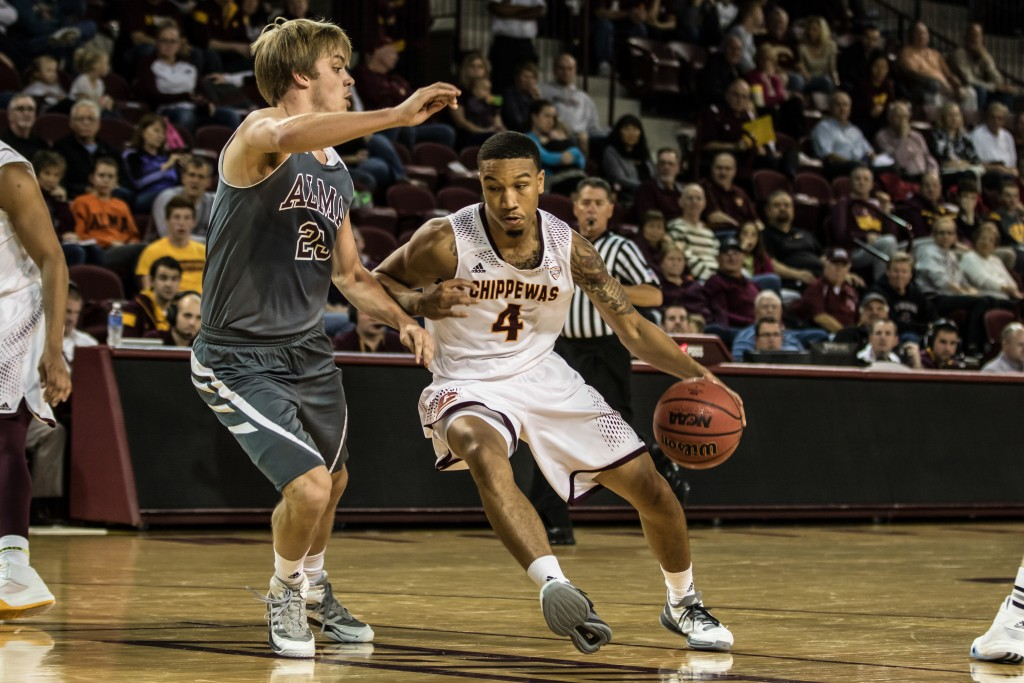 Rayshawn Simmons, 4, drives to the hoop against Trevor Gernaat, 23, during the game against Alma College at McGuirk Arena in Mt. Pleasant, Michigan, Tuesday, November 17, 2015.