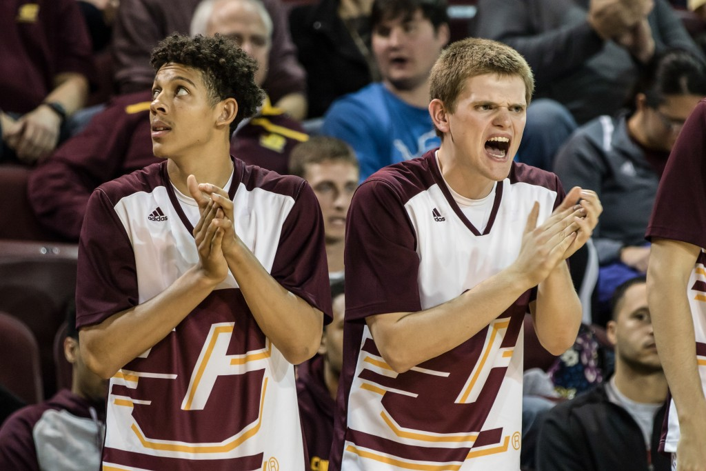 Janeau Joubert, left, and John McCarty, right, cheer on their teammates during the game against Alma College at McGuirk Arena in Mt. Pleasant, Michigan, Tuesday, November 17, 2015.