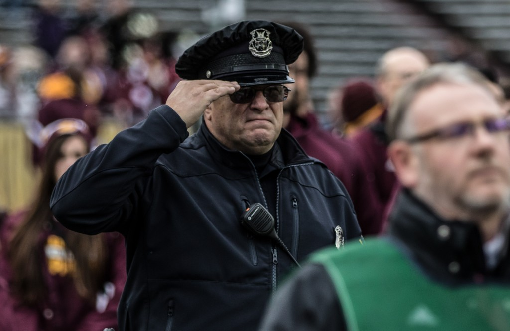 An officer salutes during the Pledge of Alligance before the game against Eastern Michigan University at Kelly / Shorts Stadium on the campus of Central Michigan University, Mt. Pleasant, Michigan, Friday, November 27, 2015.