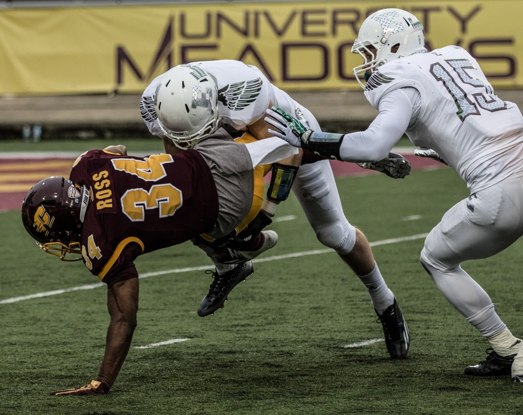 Romello Ross, 34, is taken down by a defender during the game against Eastern Michigan University at Kelly / Shorts Stadium on the campus of Central Michigan University, Mt. Pleasant, Michigan, Friday, November 27, 2015.