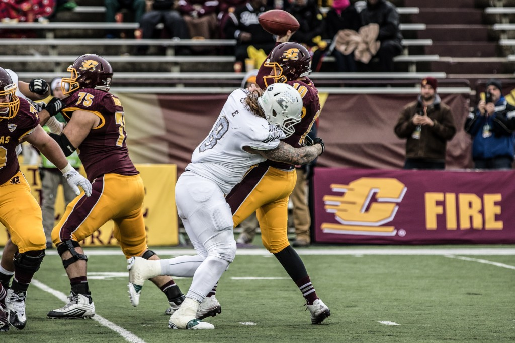 Cooper Rush, 10, looks to throw the ball while being takcled by Luke Maclean, 8, during the game against Eastern Michigan University at Kelly / Shorts Stadium on the campus of Central Michigan University, Mt. Pleasant, Michigan, Friday, November 27, 2015.
