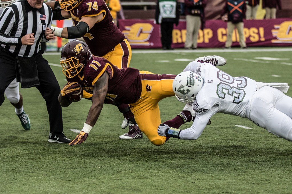 Jahray Hayes, 11, is brougt down by Jason Beck, 39, during the game against Eastern Michigan University at Kelly / Shorts Stadium on the campus of Central Michigan University, Mt. Pleasant, Michigan, Friday, November 27, 2015.